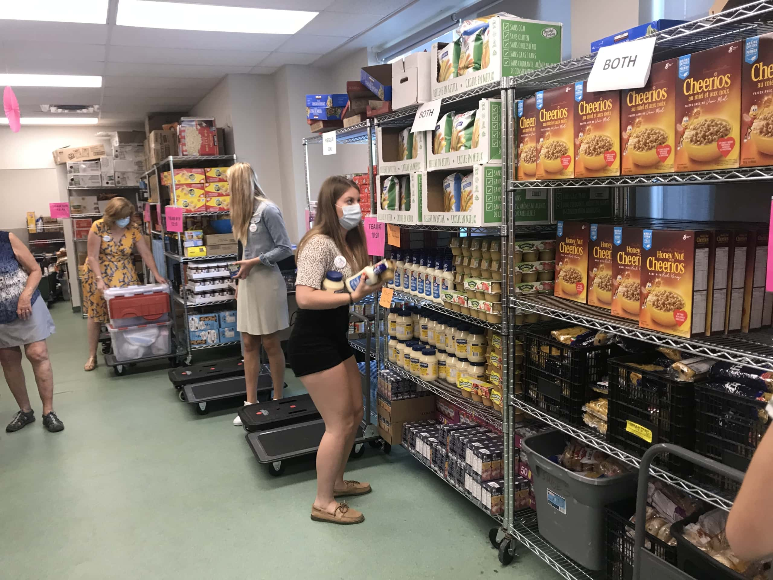 Volunteers at a grocery store select food items for boxes