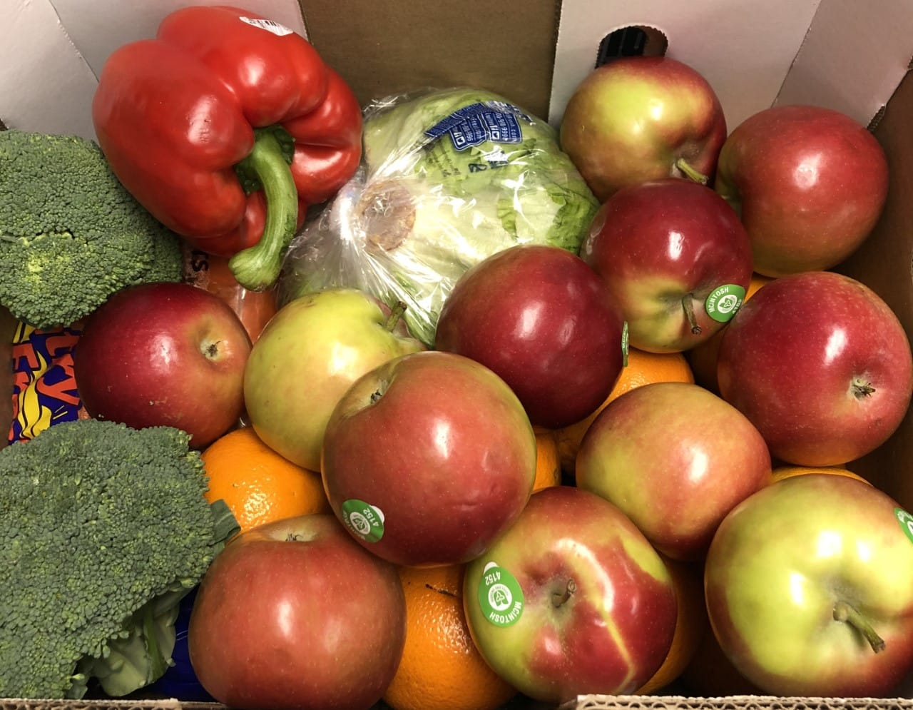 Apples, peppers, lettuce, oranges, and broccoli in a box